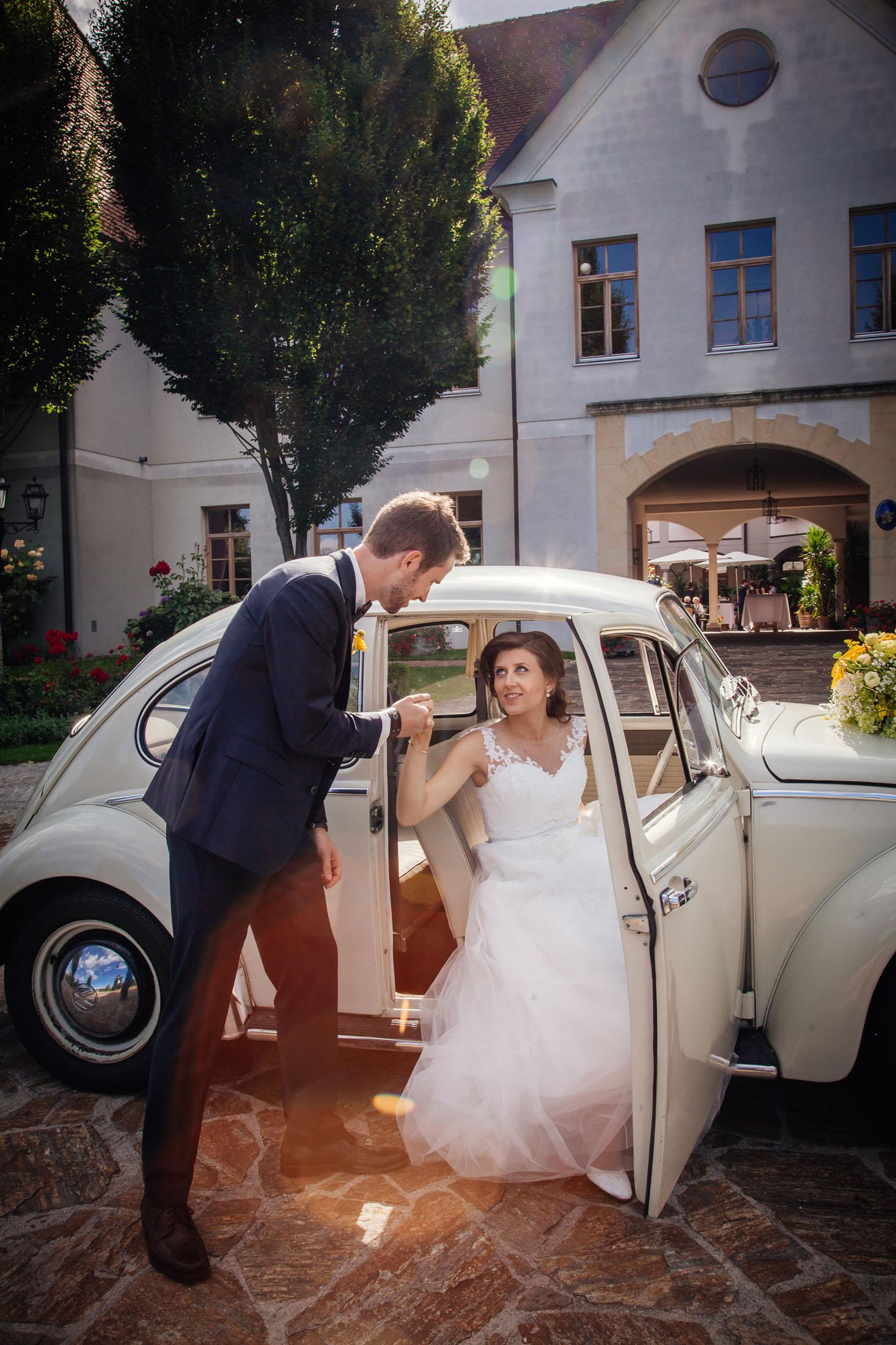 Hochzeit Karina & Johannes Braut steigt aus VW Käfer im Weinschloss Thaller