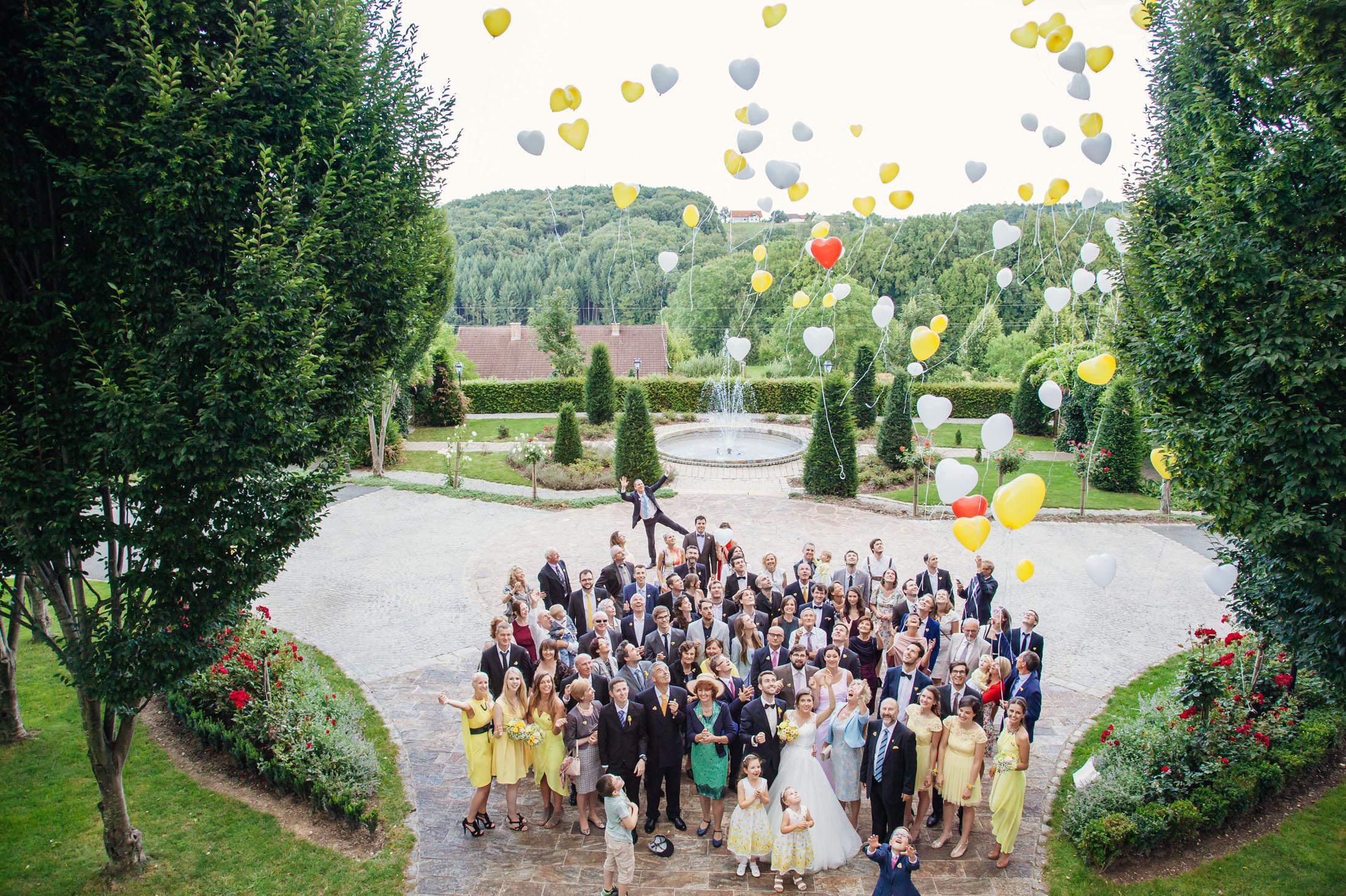 Hochzeit Karina & Johannes Gruppenfoto Hochzeitgesellschaft mit Ballons im Weinschloss Thaller
